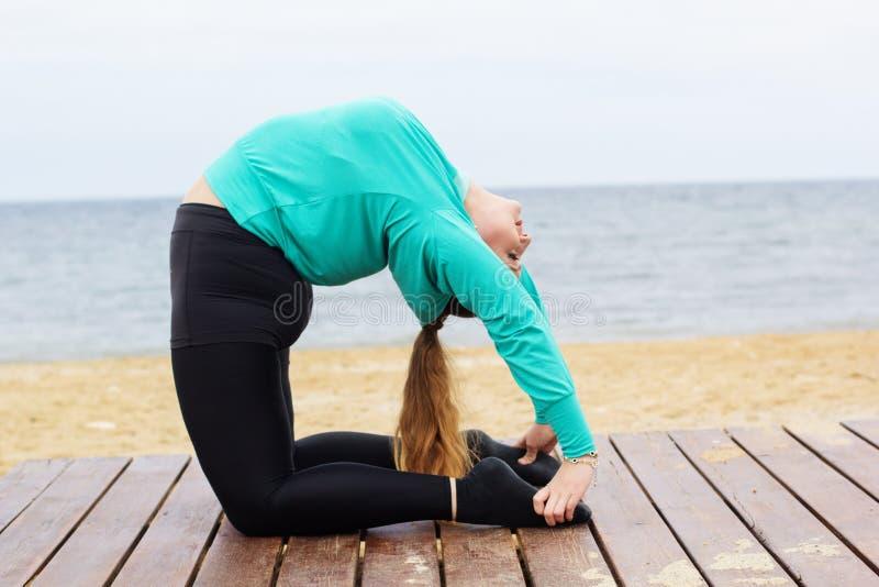 Femme faisant l'asana de yoga de hatha près de la mer photo stock