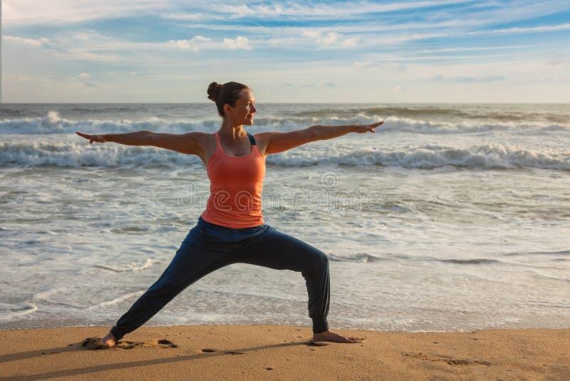 Femme faisant l'asana Virabhadrasana de yoga 1 pose de guerrier sur la plage dessus photo libre de droits