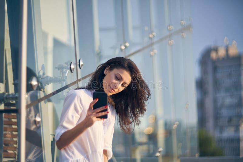 Femme faisant l'autoportrait avec son téléphone intelligent au-dessus du bureau moderne buiding image libre de droits