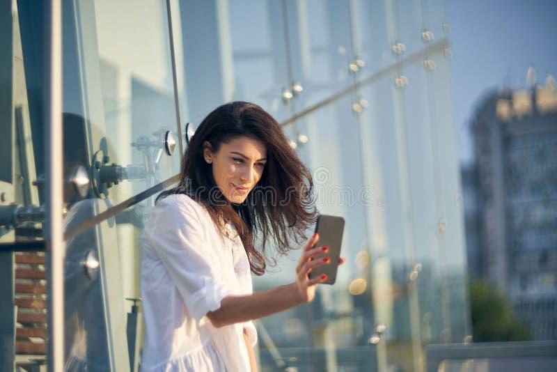 Femme faisant l'autoportrait avec son téléphone intelligent au-dessus du bureau moderne buiding images libres de droits
