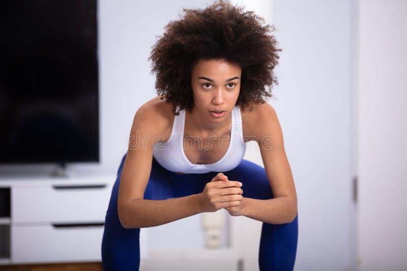 Femme faisant l'exercice accroupi photographie stock libre de droits