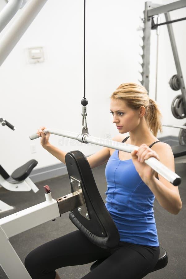 Femme faisant l'exercice de poids dans le club de santé photos stock
