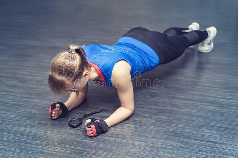 Femme faisant l'exercice de pousée Séance d'entraînement faisante femelle forte de crossfit la blonde se tient sur ses coudes et  photos libres de droits