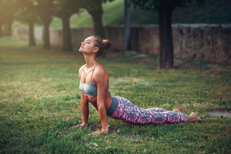 Femme faisant l'exercice de yoga en parc d'été photos libres de droits