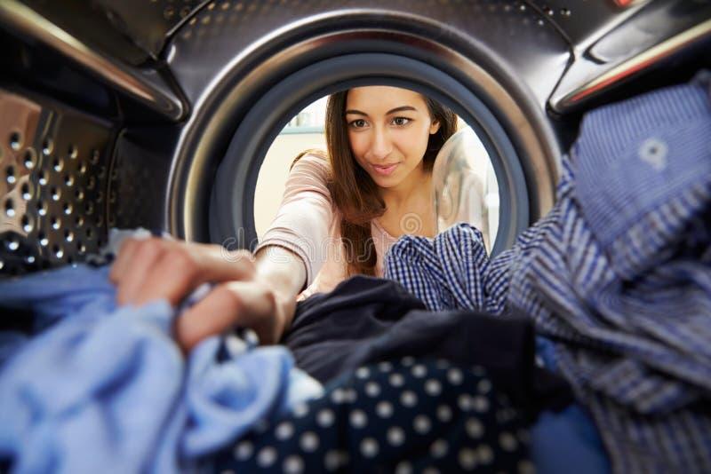 Femme faisant la blanchisserie atteignant la machine à laver intérieure image stock
