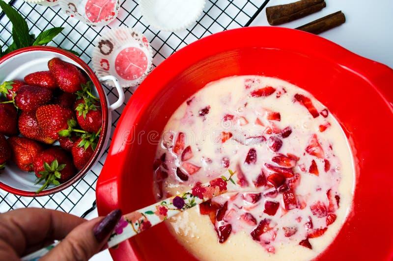 Femme faisant la crème de fraises pour un gâteau image libre de droits