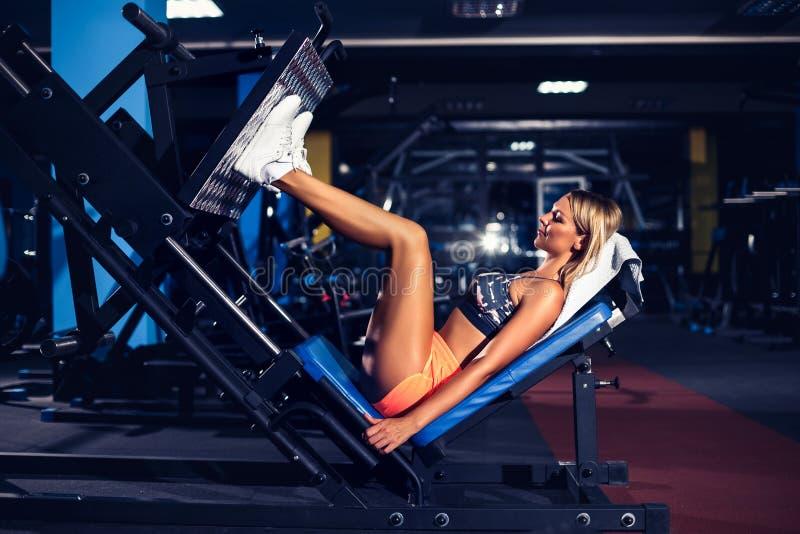 Femme faisant la formation de forme physique sur une machine de poussée d'extension de jambe avec des poids photos stock
