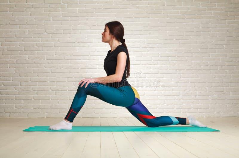 Femme faisant la forme physique étirant la séance d'entraînement d'exercices à l'intérieur dans le mode de vie sain de corps de s photographie stock