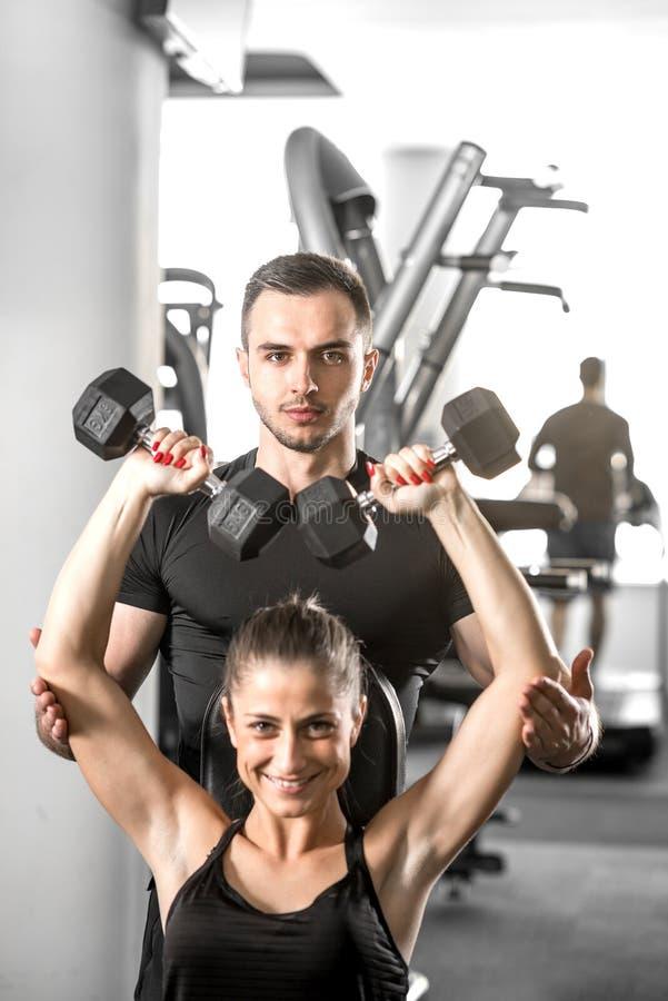 Femme faisant la forme physique avec l'aide personnelle d'entraîneur photographie stock