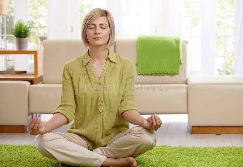 Femme faisant la méditation de yoga à la maison image libre de droits