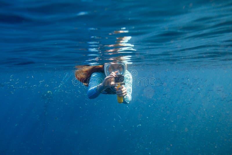 Femme faisant la photo sous l'eau Fille naviguant au schnorchel dans le masque de plein-visage Prise d'air avec des poissons sous images stock