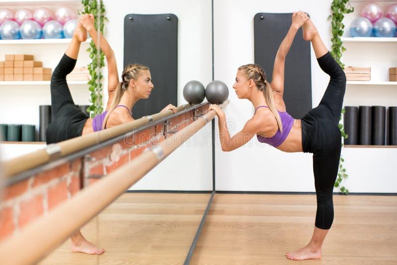 Femme faisant la pose de danse tout en tenant le barre au gymnase photographie stock