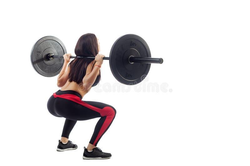 Femme faisant la posture accroupie avec un barbell photos libres de droits