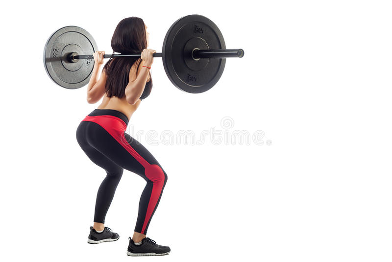 Femme faisant la posture accroupie avec un barbell image libre de droits
