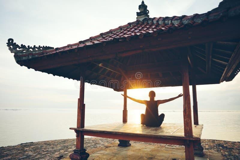 Femme faisant la pratique en matière de forme physique dans l'abri du soleil près de l'océan images stock