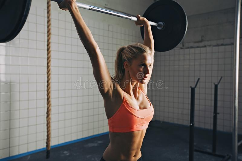 Femme faisant le levage de barbell de crossfit photo stock