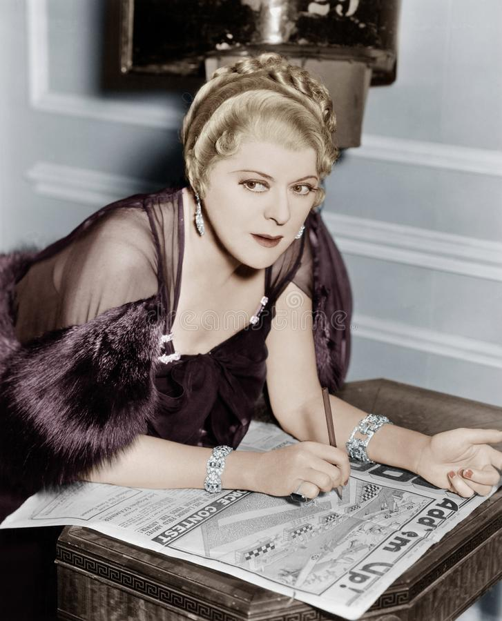Femme faisant le puzzle en journal (toutes les personnes représentées ne sont pas plus long vivantes et aucun domaine n'existe Ga image stock