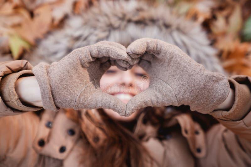 Femme faisant le symbole de coeur avec des mains sur la nature photo stock
