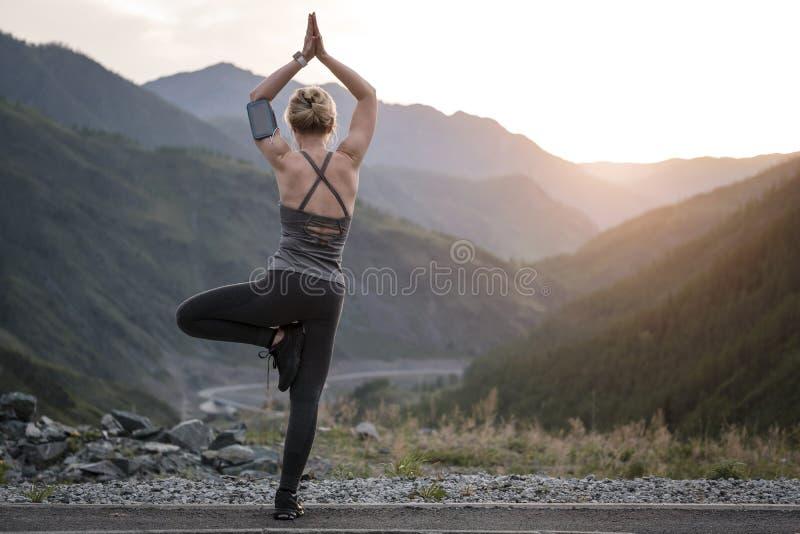 Femme faisant le yoga au coucher du soleil Sports et récréation image stock