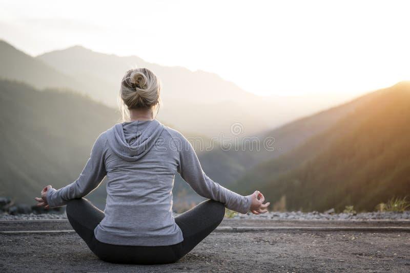 Femme faisant le yoga au coucher du soleil Sports et récréation photos libres de droits