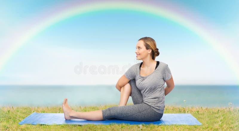 Femme faisant le yoga dans la pose de torsion sur le tapis image stock