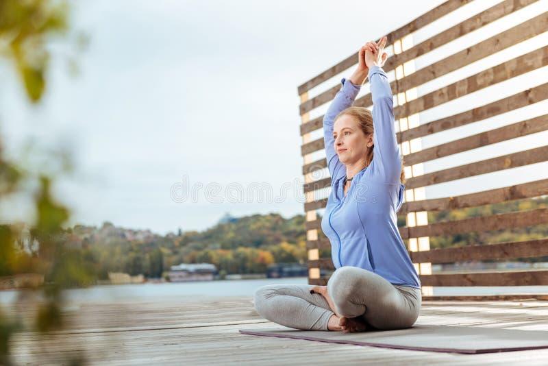 Femme faisant le yoga de matin près de la rivière photo libre de droits