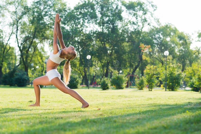 Femme faisant le yoga en parc images libres de droits