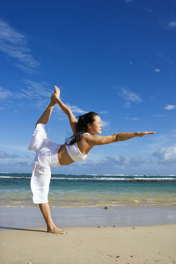 Femme faisant le yoga sur la plage photographie stock