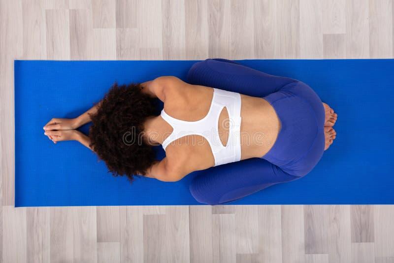 Femme faisant le yoga sur le tapis de forme physique photos libres de droits