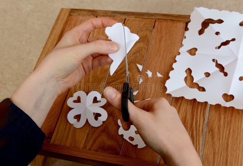 Femme faisant les flocons de neige de papier à une table en bois de métier image libre de droits