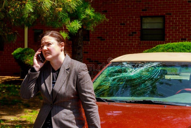 Femme faisant un appel téléphonique par le pare-brise endommagé après un accident de voiture images stock