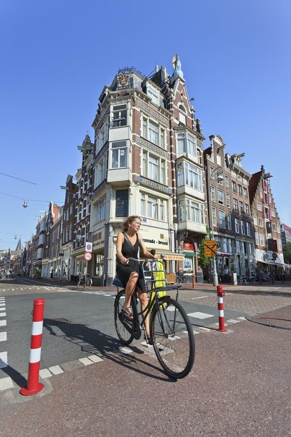 Femme faisant un cycle dans la vieille ville d'Amsterdam. photographie stock libre de droits