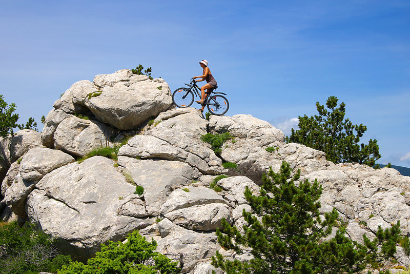 Femme faisant un cycle dans les montagnes image libre de droits