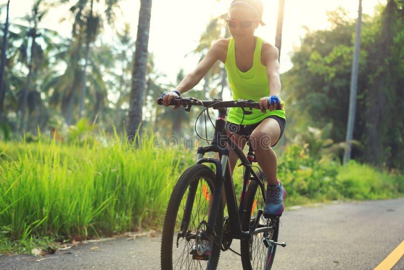 Femme faisant un cycle sur la traînée tropicale de forêt photo libre de droits
