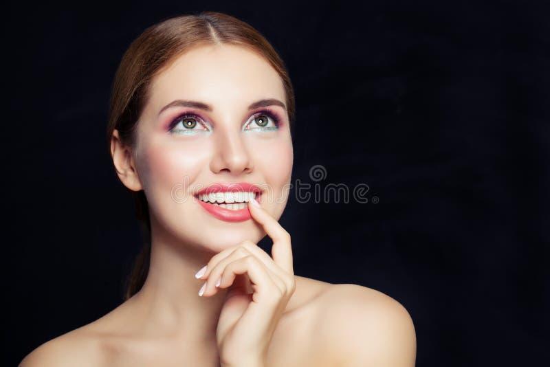 Femme fascinante avec le maquillage recherchant sur le fond noir avec l'espace de copie images stock