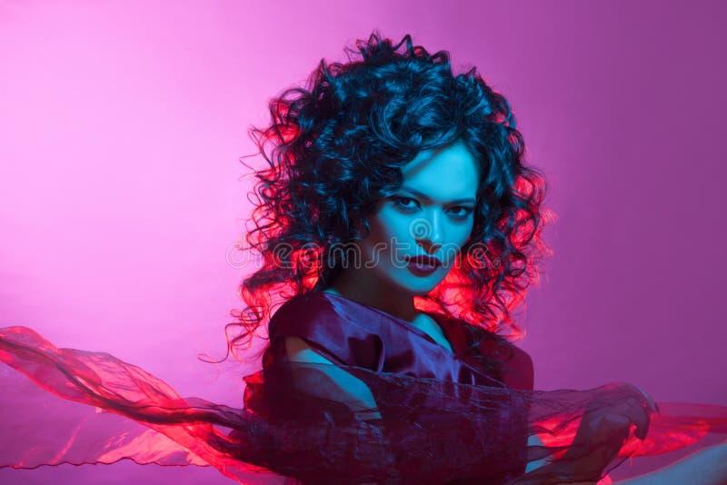 Femme fatale het dansen, portret in Studio met het heldere stemmen, blauwe en rode kleur stock foto