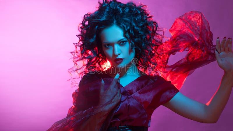 Femme fatale het dansen, portret in Studio met het heldere stemmen, blauwe en rode kleur stock afbeelding