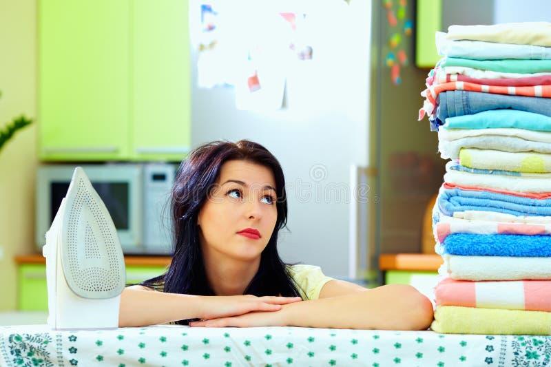 Femme fatiguée après avoir repassé des vêtements, intérieur de maison image libre de droits