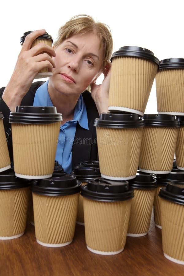 Femme fatiguée d'affaires et tasses jetables image stock