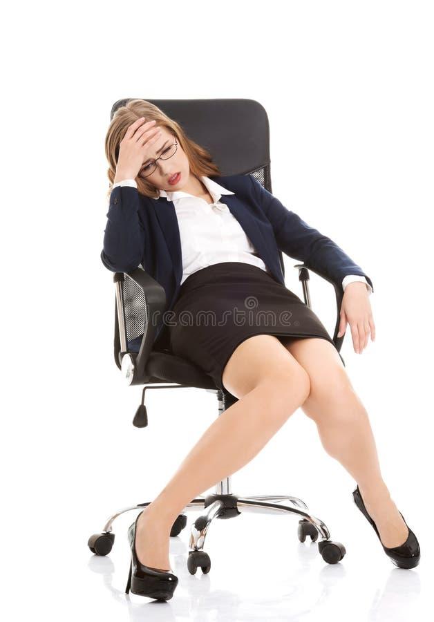 Femme fatiguée d'affaires sur une chaise photographie stock libre de droits
