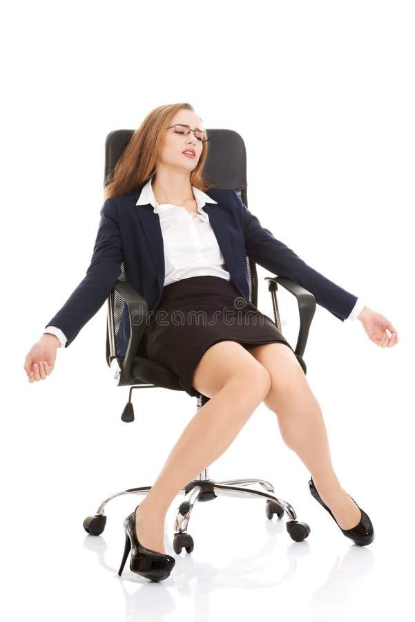 Femme fatiguée d'affaires sur une chaise image stock