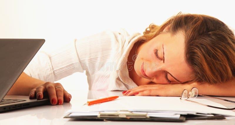 Femme fatiguée dormant sur le lieu de travail (travail excessif, surmenage, image libre de droits