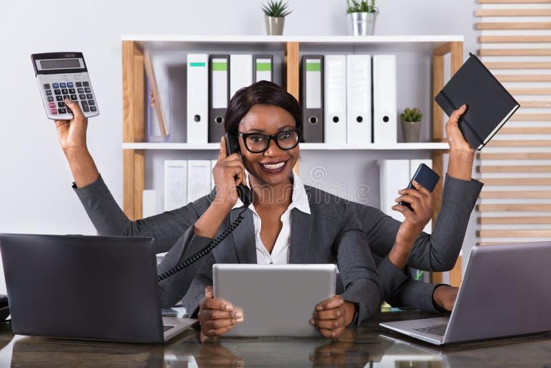 Femme fatiguée effectuant le travail multitâche sur l'ordinateur portable images stock