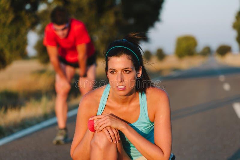 Femme fatiguée et homme se reposant après épreuve sur route courante photo stock