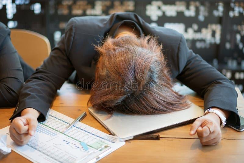 Femme fatiguée et surchargée d'affaires dormant sur le bureau photographie stock