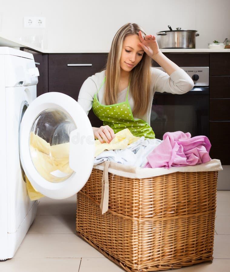 Femme fatiguée faisant la blanchisserie avec la machine à laver images stock
