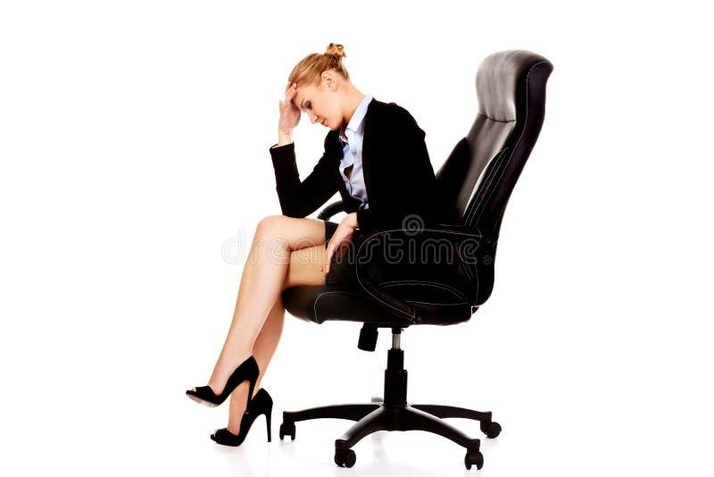 Femme fatiguée ou inquiétée d'affaires s'asseyant sur le fauteuil image stock