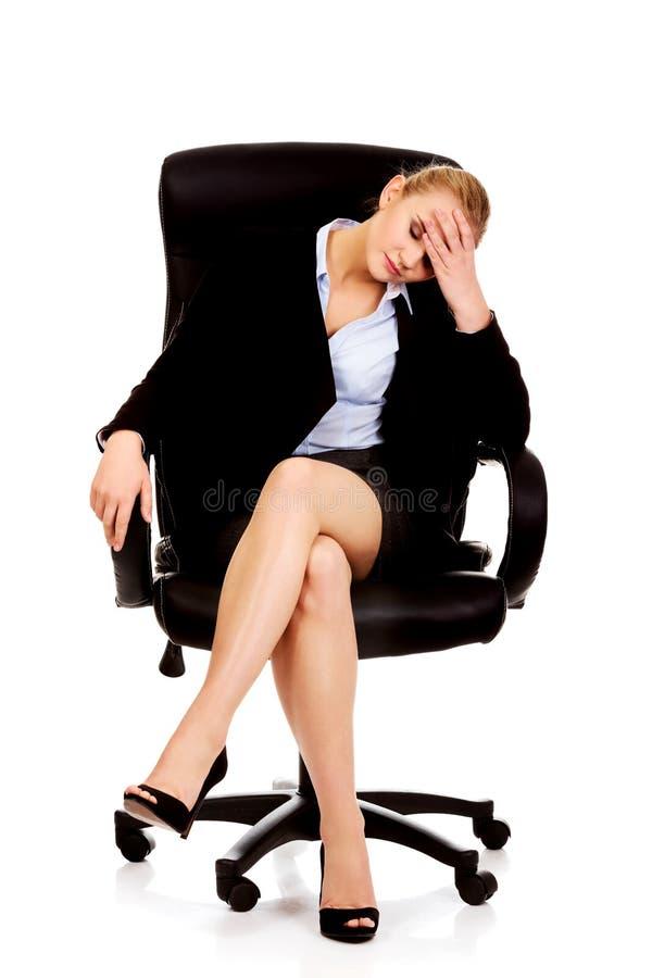 Femme fatiguée ou inquiétée d'affaires s'asseyant sur le fauteuil photo stock