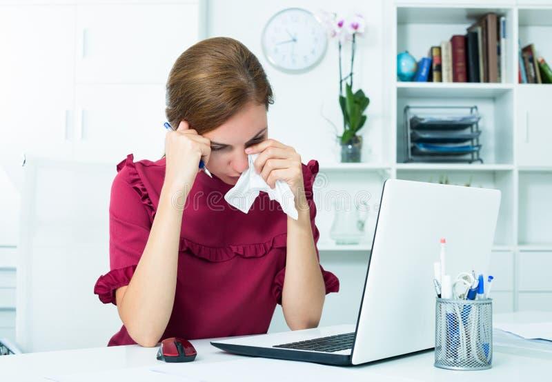 Femme fatiguée pleurant au travail images stock