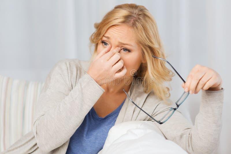 Femme fatiguée prenant l'offhome de lunettes photos libres de droits